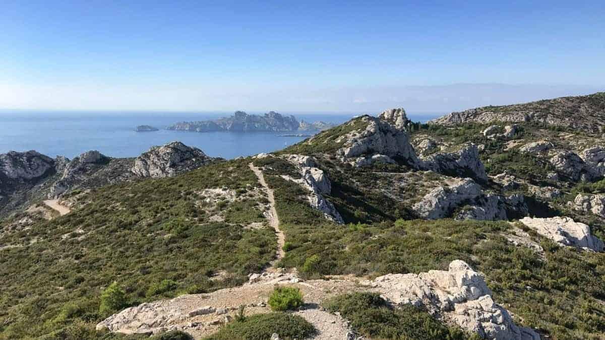 Küstenwanderweg Marseille Etappe 5 schroffe Felsen sattes Grün blauer Himmel und das Meer im Parc National des Calanques
